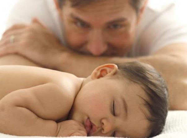 папа смотрит на спящего младенца