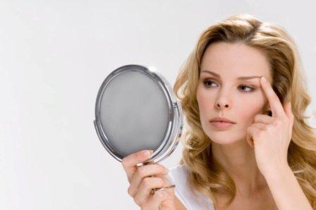 Девушка смотрит в зеркало, разглядывание внешности