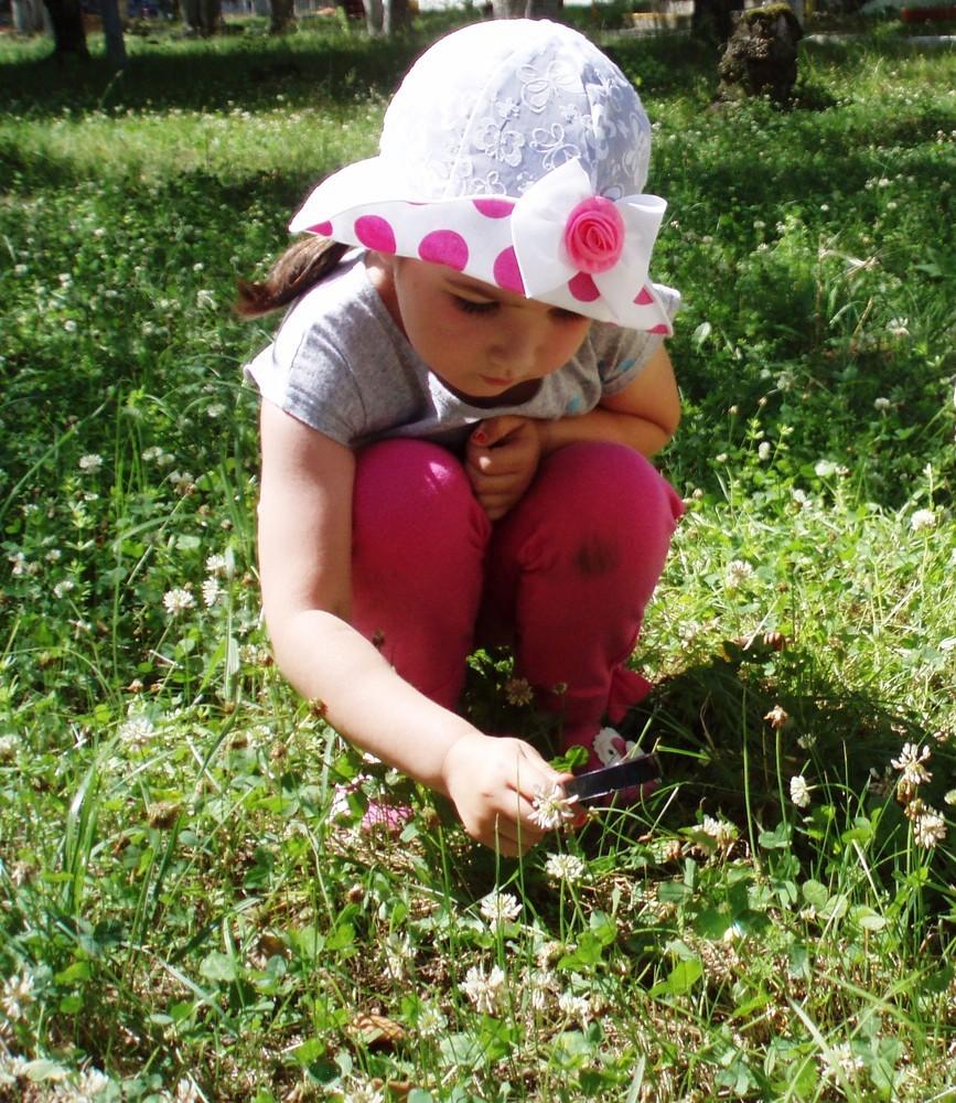 девочка через лупу смотрит в траву