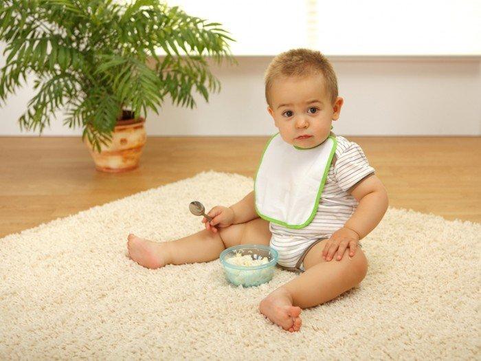 ребенок сидит на паласе в комнате, правила выбора коврового покрытия в детскую комнату