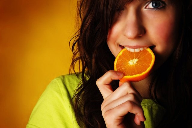 девушка кушает апельсин, продукты помогут улучшить красоту кожи