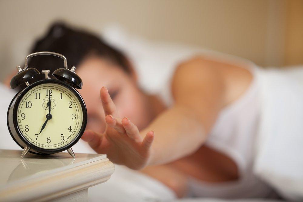 женщина выключает будильник, как вставать и ложиться вовремя