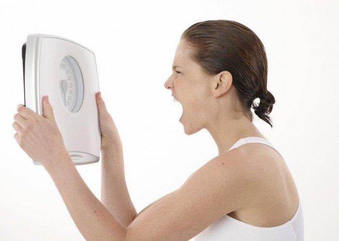 девушка злится на весы, что съесть, чтобы не поправиться