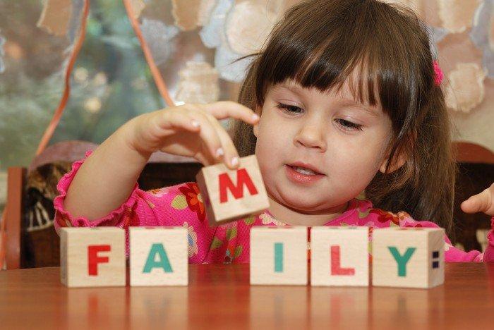 девочка складывает кубики с английскими буквами