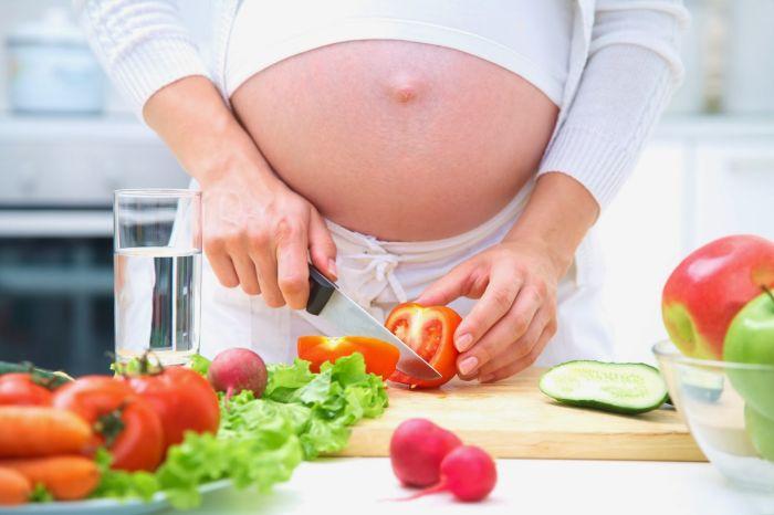 беременная женщина режет овощи для салата