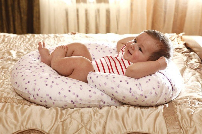 малыш лежит на подушке для кормления