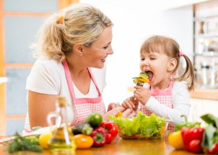 мама с дочкой кушают овощи