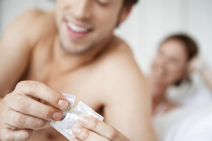 мужчина достает презерватив