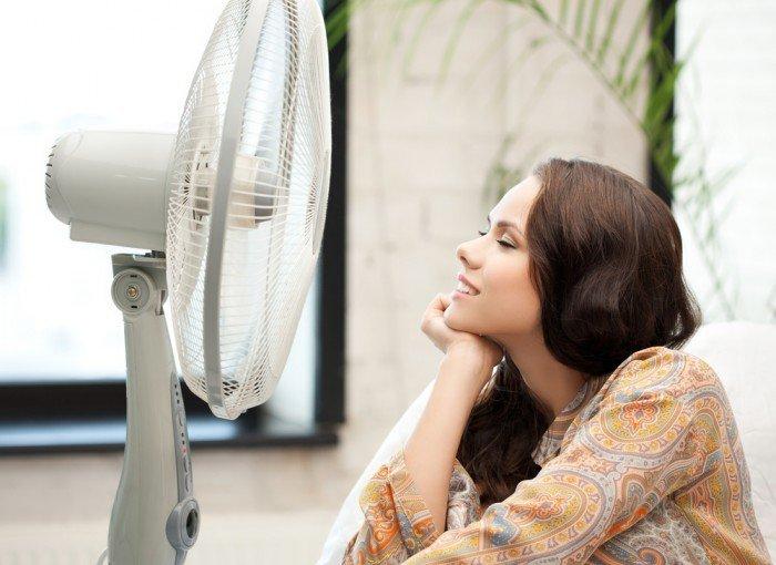 женщина сидит перед вентилятором