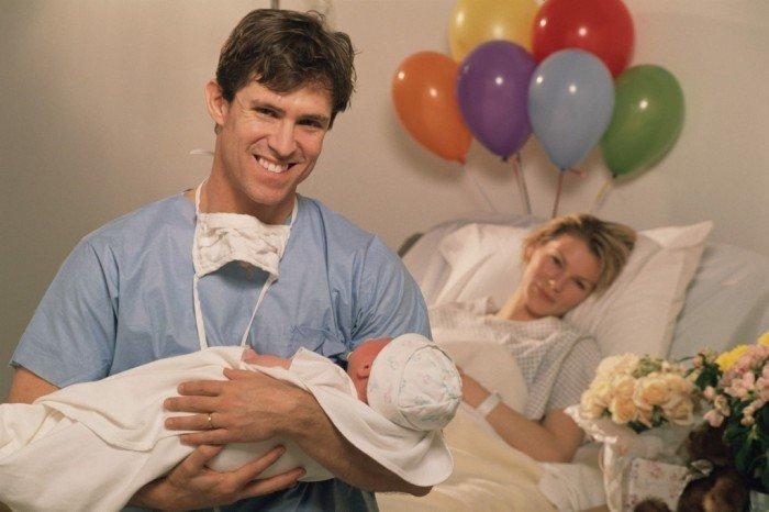 Партнерские роды - счастливый отец принимает на руки своего новорожденного малыша