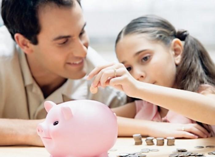 девочка кладет деньги в копилку, финансовая грамотность ребенка