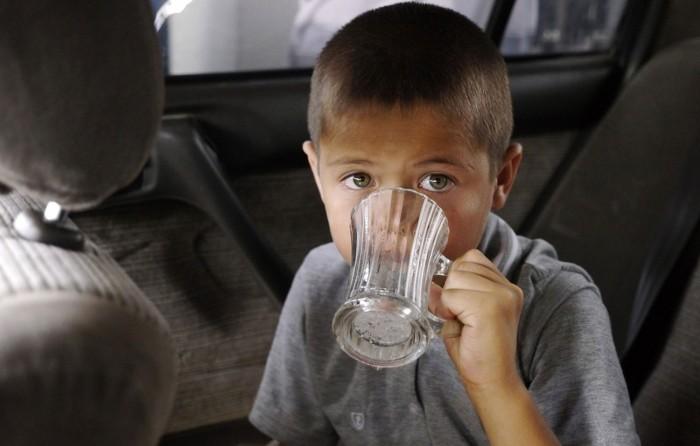 у ребенка икота, мальчик пьет воду для избавления от икоты