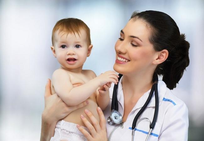 Женщина-врач держит на руках малыша