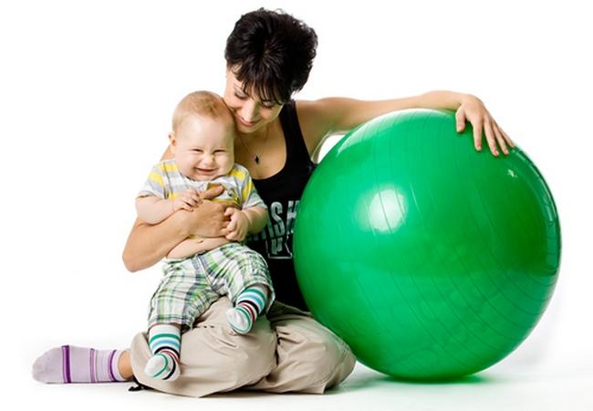 Мама и малыш сидят возле гимнастического мяча