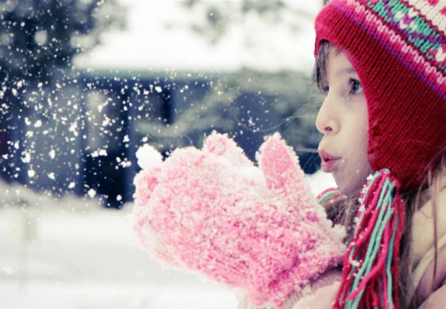 Девочка дует на снежинки