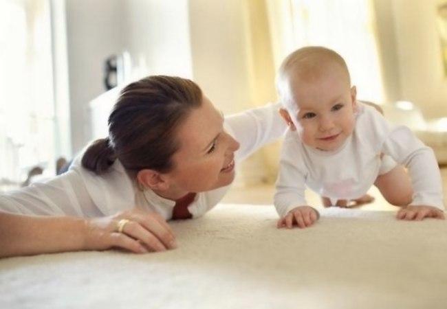 Мама помогает малышу научиться ползать