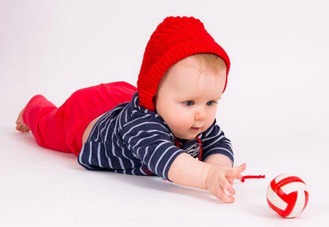 Малыш, лёжа на животике, тянется за игрушкой
