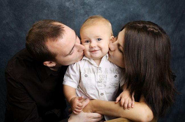 Мама и папа целуют своего малыша