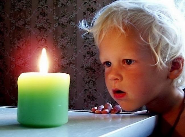 Мальчик смотрит на свечу