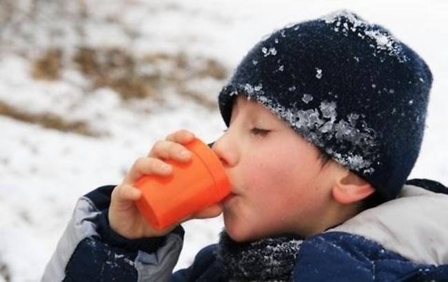Мальчик пьёт тёплый чай во время зимней прогулки