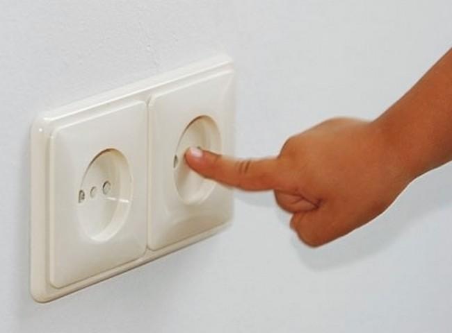 Ребёнок трогает пальчиком розетку