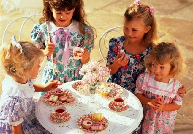 Девочки пьют чай со сладостями