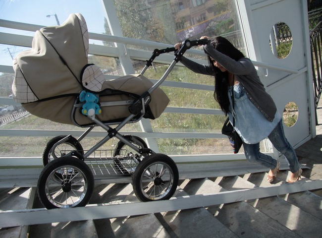 Мама катит коляску-люльку по пандусу