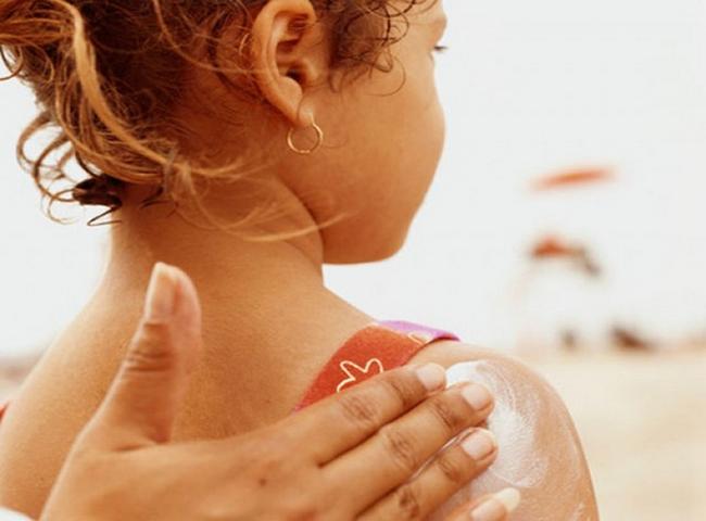 Мама натирает девочку кремом от загара