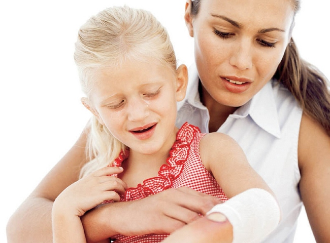 Мама накладывает дочке холодный компресс при ожоге