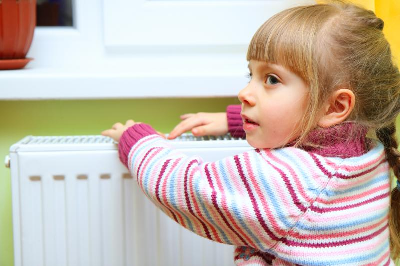 Девочка греет руки возле обогревателя