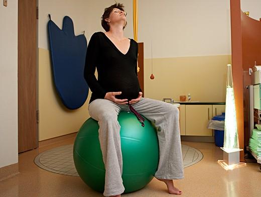 Беременная сидит на гимнастическом мяче