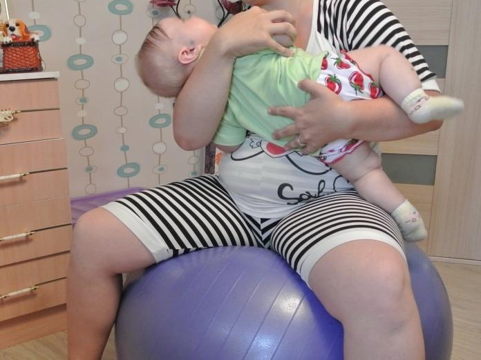 Мама тренируется на фитболе с малышом на руках