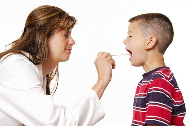 Женщина-доктор осматривает горло мальчику