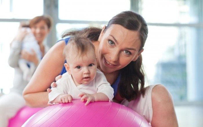 Мама положила ребёнка на гимнастический мяч