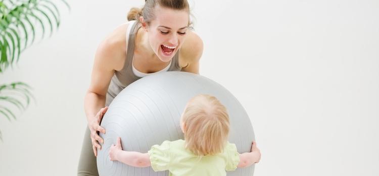 Мама и малыш играют с гимнастическим мячом