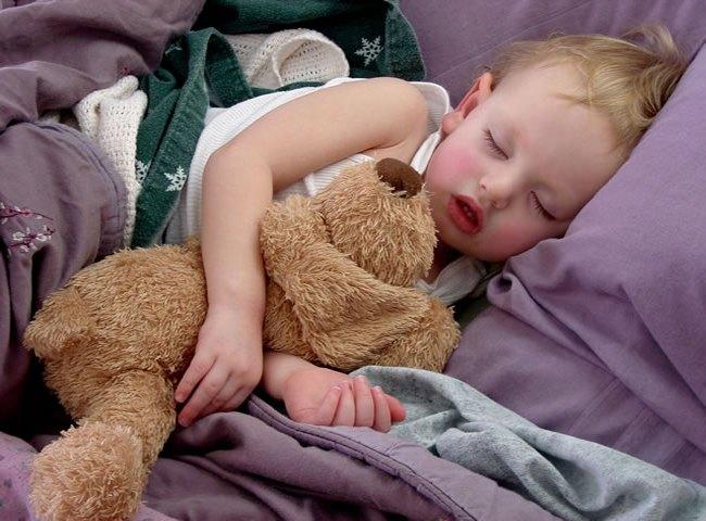 Ребёнок спит с мягкой игрушкой