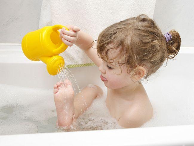 Девочка играет в ванной лейкой