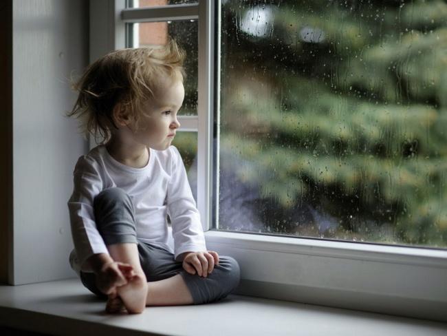 Ребёнок сидит на подоконнике и смотрит в окно