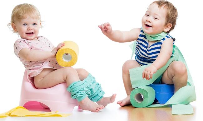 Мальчик и девочка играют туалетной бумагой, сидя на горшках