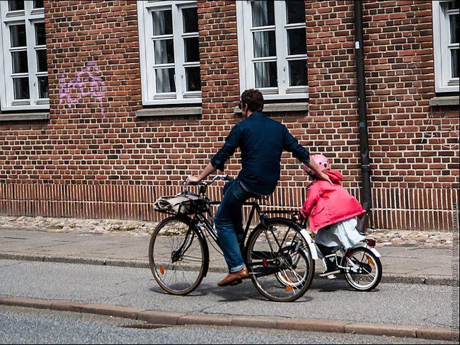 Пап с дочерью катаются на велосипедах