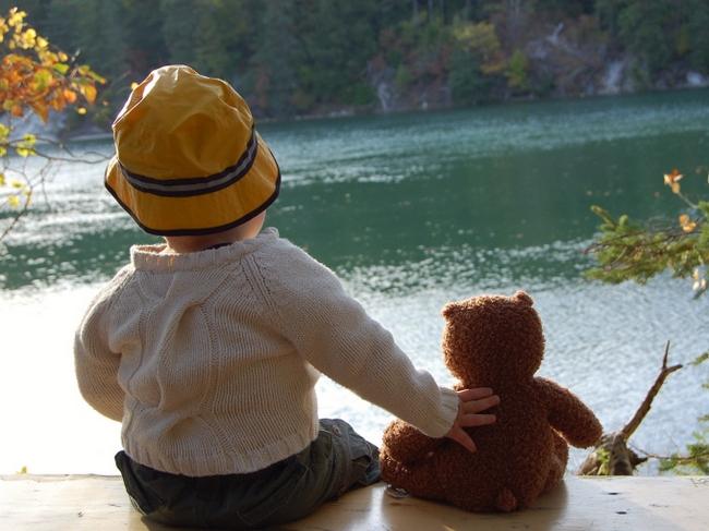 Мальчик с медвежонком сидит на берегу реки