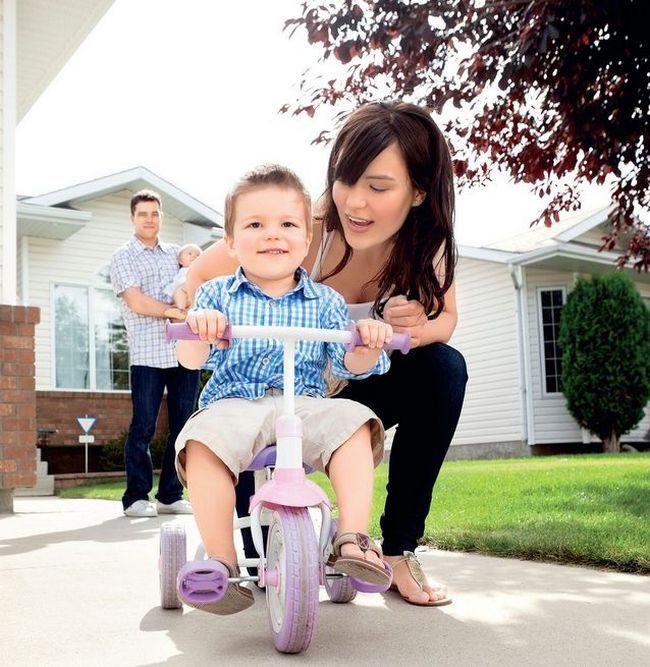 Мама учит малыша кататься на трёхколёсном велосипеде