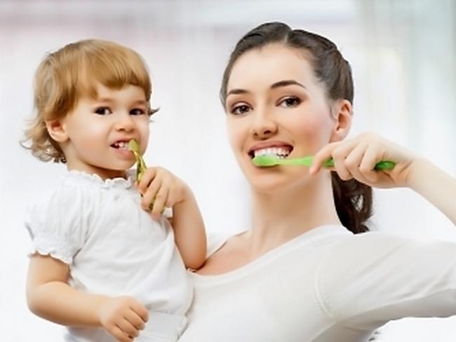 Мама показывает ребёнку, как чистить зубы
