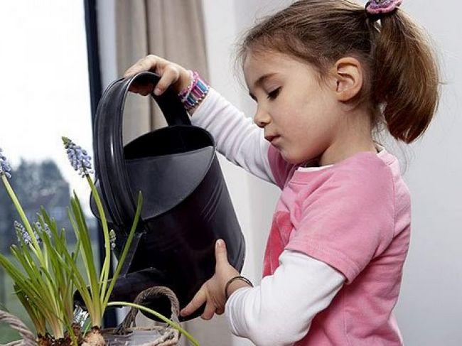 Девочка поливает цветы