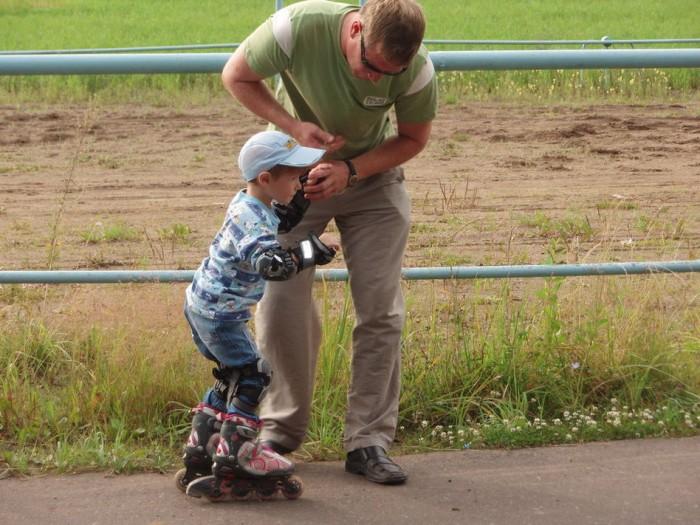 Папа учит сына кататься на роликах