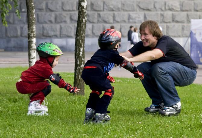 Папа учит детей кататься на роликах