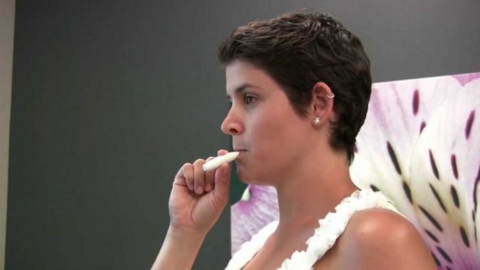 Девушка использует никотиновый ингалятор