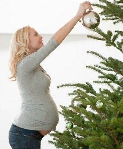 Будущая мама украшает ёлку