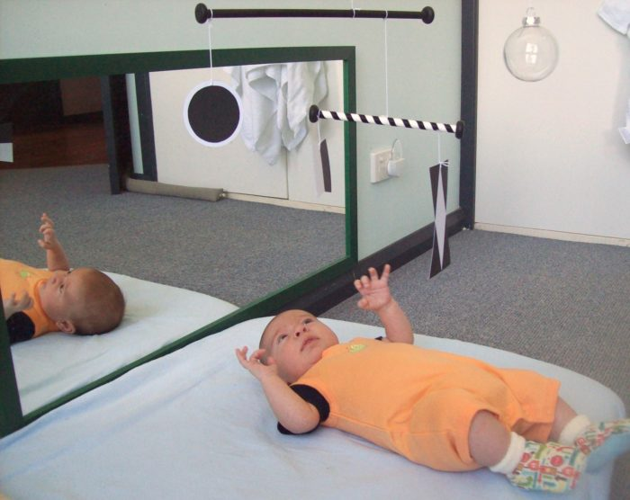 Ребёнок наблюдает за мобилем Мунари