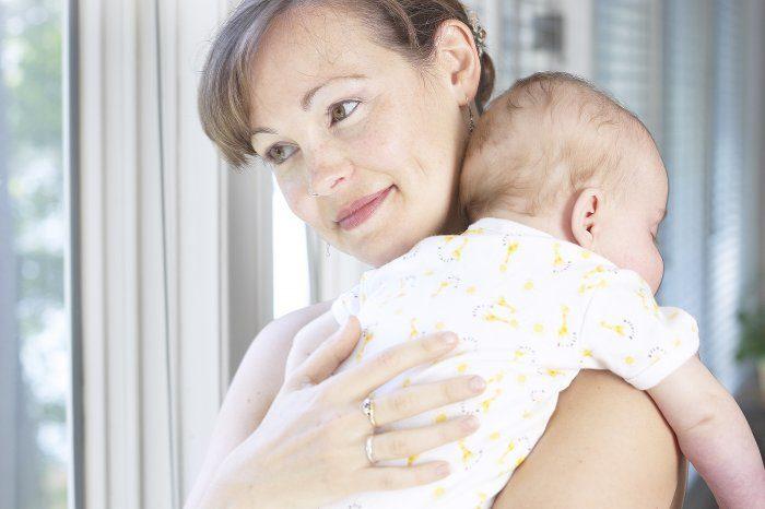 Мама держит малыша, который запрокинул ручку на её плечо